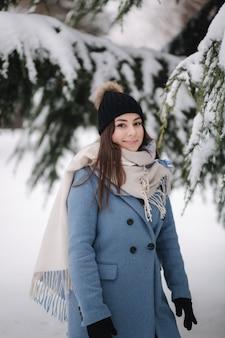 Bella donna in cappotto blu che cammina nel bosco in una giornata invernale nevosa