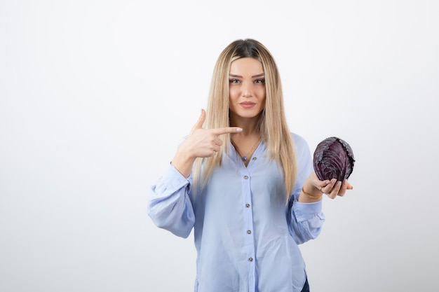 Bella donna in abito blu che punta al cavolo viola sul muro bianco.