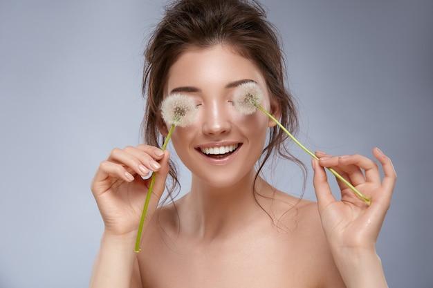 Pretty woman chiudendo gli occhi con fiori di tarassaco e sorridente