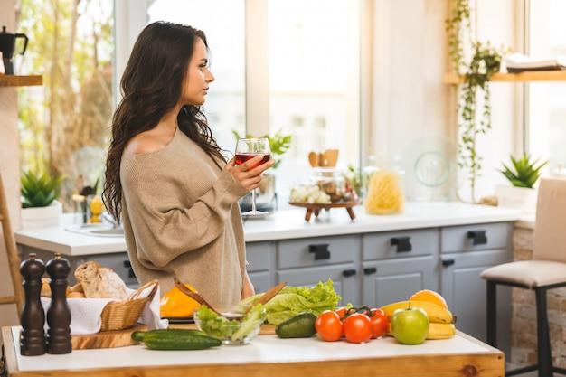 Donna graziosa che cucina e che beve un certo vino a casa in cucina.