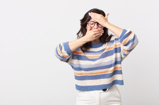 Bella donna che copre il viso con entrambe le mani dicendo no alla telecamera! rifiutare le foto o vietare le foto