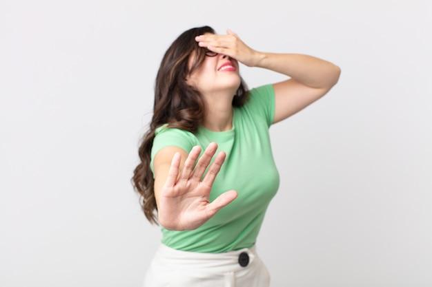 Bella donna che copre il viso con la mano e mette l'altra mano davanti per fermare la fotocamera, rifiutando foto o immagini