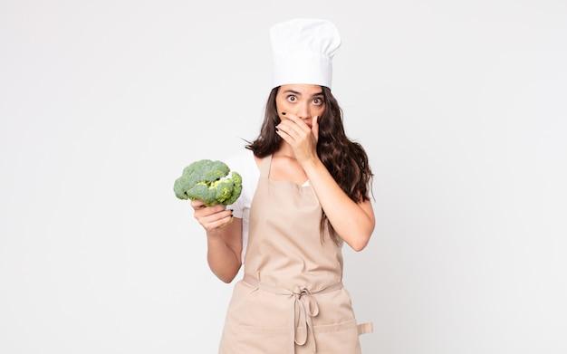 Bella donna che copre la bocca con le mani con uno scioccato che indossa un grembiule e tiene in mano un broccolo