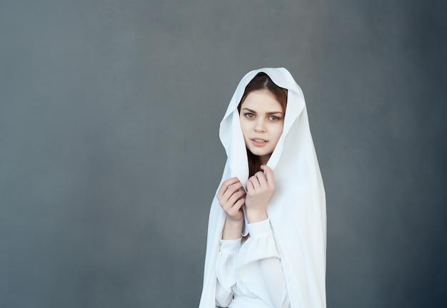 Bella donna si copre con un panno bianco con uno studio di moda per il trucco della testa