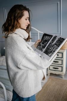 Bella donna in accogliente maglione grigio sfogliando una rivista in camera da letto. studentessa carina guardando attraverso il libro.