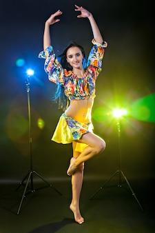 Bella donna che balla tra le luci davanti a uno sfondo nero black