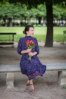 Bella donna in un abito blu scuro seduto su una sedia nel parco