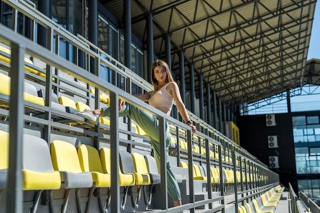 Bella donna che fa esercizi mattutini rilassanti sulla tribuna dello stadio, prima della giornata lavorativa