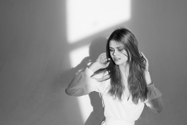 Donna graziosa in studio di posa della foto in bianco e nero del vestito