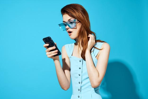 Bella donna in un vestito e occhiali con il telefono in mano isolato sfondo