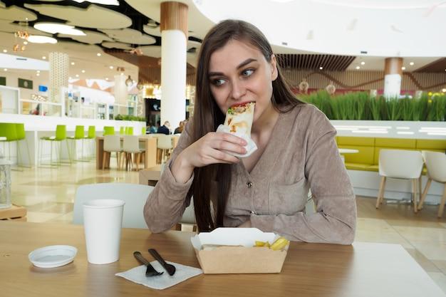 Bella donna che mangia fast food in un ristorante