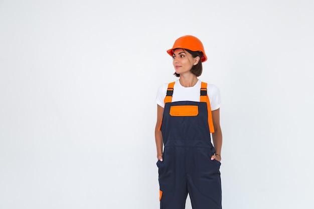 L'ingegnere grazioso della donna nella costruzione del casco protettivo sul sorriso sicuro bianco ha attraversato le braccia