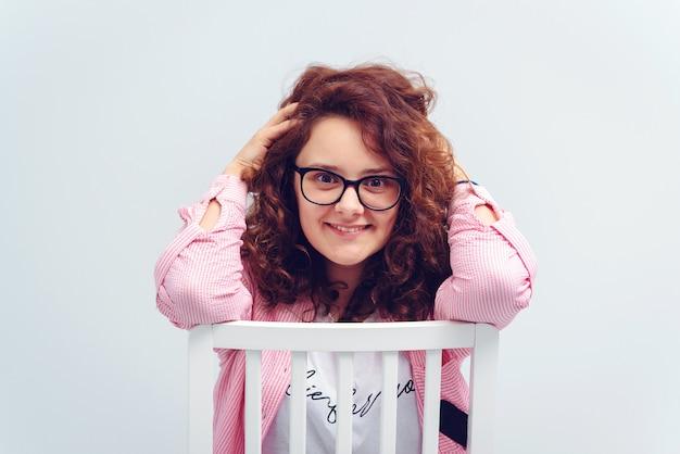Donna graziosa in occhiali che sorride e che si siede sulla sedia.