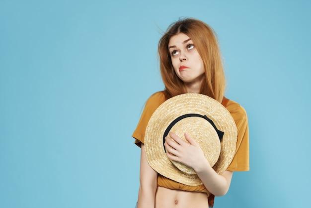 Studio della tenuta del cappello dei vestiti di moda della donna graziosa