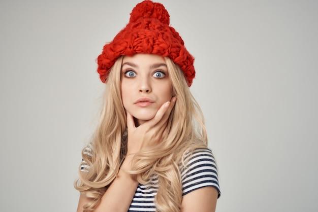 Bella donna in abiti alla moda cappello rosso sfondo chiaro