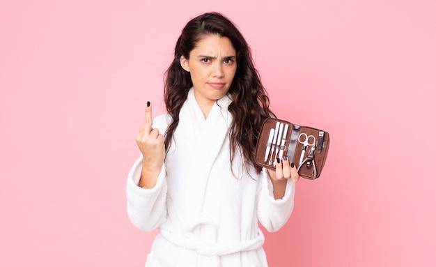 Bella donna che si sente arrabbiata, infastidita, ribelle e aggressiva e tiene in mano una borsa per il trucco con strumenti per le unghie