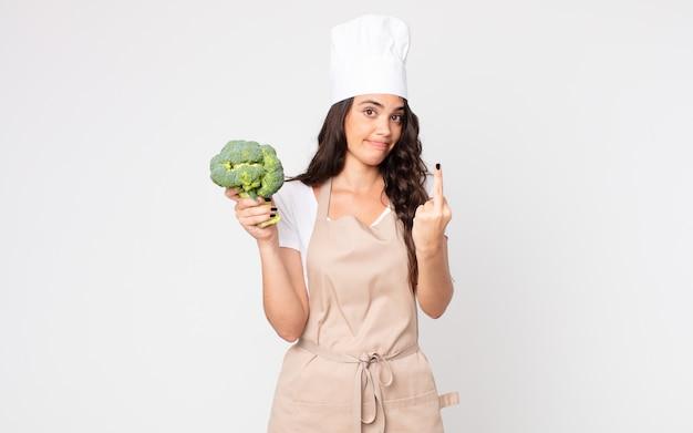 Bella donna che si sente arrabbiata, infastidita, ribelle e aggressiva che indossa un grembiule e tiene in mano un broccolo