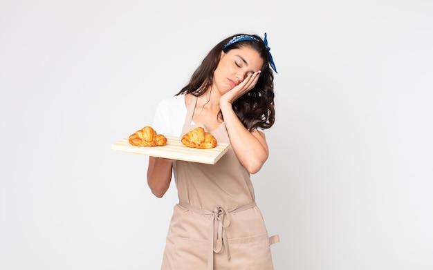 Bella donna che si sente annoiata, frustrata e assonnata dopo una noiosa e con in mano un vassoio di croissant