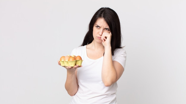 Bella donna che si sente annoiata, frustrata e assonnata dopo una noiosa e con in mano una scatola di uova