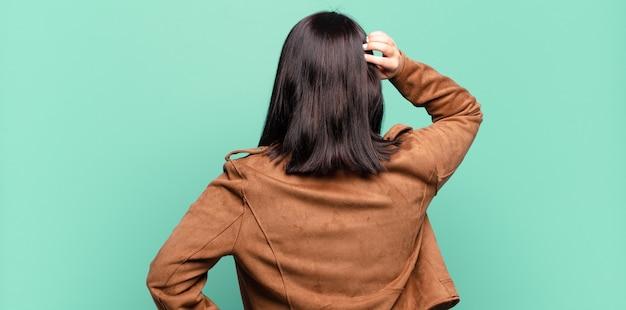 Bella donna che si sente incapace e confusa, pensando a una soluzione, con la mano sul fianco e l'altra sulla testa, vista posteriore