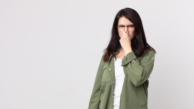 Bella donna che si sente disgustata, tiene il naso per evitare di annusare un fetore sgradevole e sgradevole