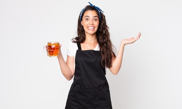 Bella donna che si sente estremamente scioccata e sorpresa e tiene in mano una pinta di birra