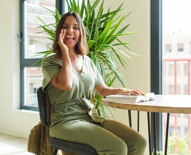 Bella donna che si sente felice, eccitata e positiva, gridando con le mani vicino alla bocca, chiamando
