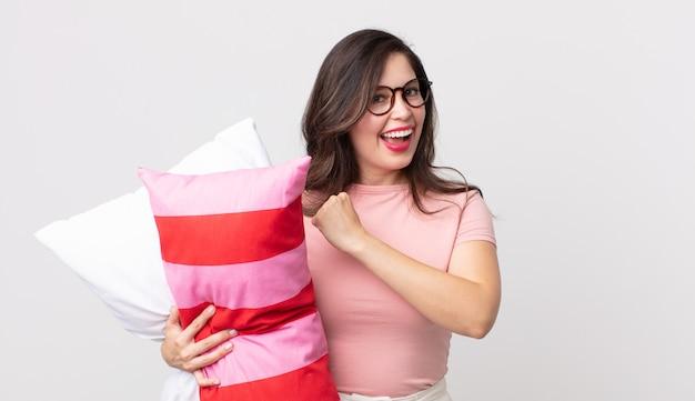 Bella donna che si sente felice e affronta una sfida o festeggia indossando un pigiama e tenendo in mano un cuscino