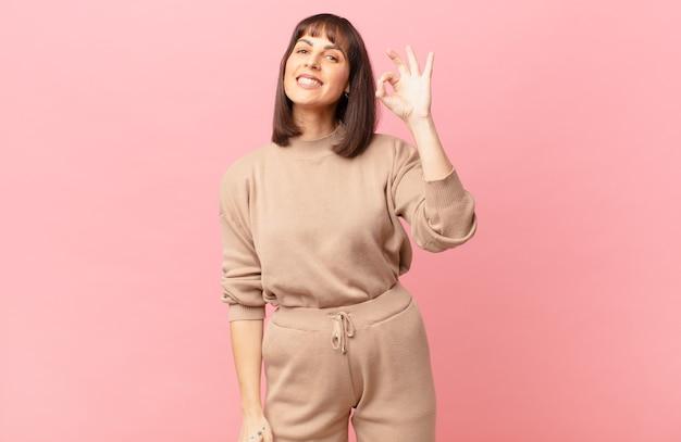 Bella donna che si sente felice, rilassata e soddisfatta, mostrando approvazione con un gesto ok, sorridendo