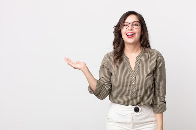 Bella donna che si sente felice, sorpresa e allegra, sorridente con atteggiamento positivo, realizzando una soluzione o un'idea
