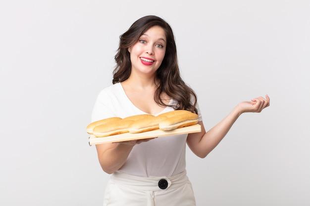 Bella donna che si sente felice, sorpresa di realizzare una soluzione o un'idea e con in mano un vassoio per il pane