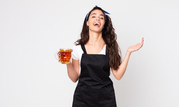 Bella donna che si sente felice, sorpresa di realizzare una soluzione o un'idea e con in mano una pinta di birra