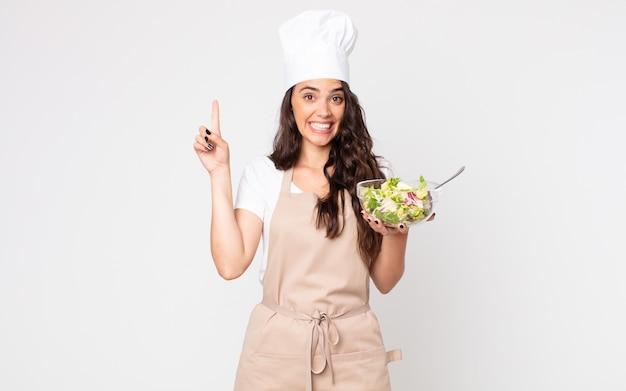 Bella donna che si sente un genio felice ed eccitato dopo aver realizzato un'idea indossando un grembiule e tenendo in mano un'insalata