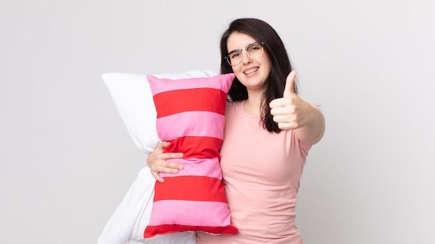 Bella donna che si sente orgogliosa, sorride positivamente con i pollici in su indossando il pigiama e tenendo in mano un cuscino