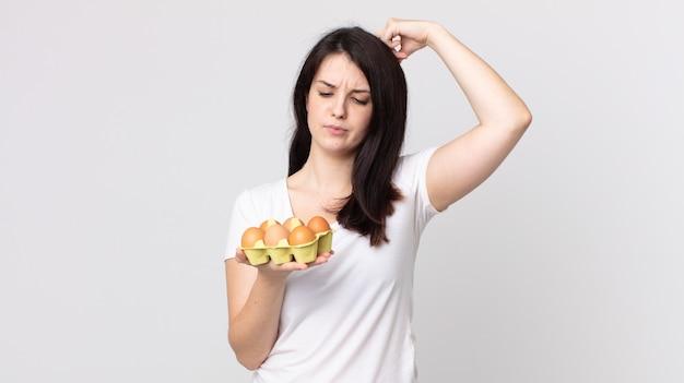 Bella donna che si sente perplessa e confusa, si gratta la testa e tiene in mano una scatola di uova