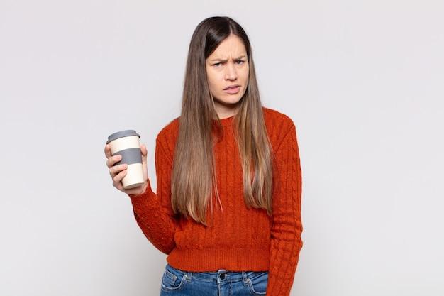 Bella donna che si sente perplessa e confusa, con un'espressione stupida e sbalordita che guarda qualcosa di inaspettato