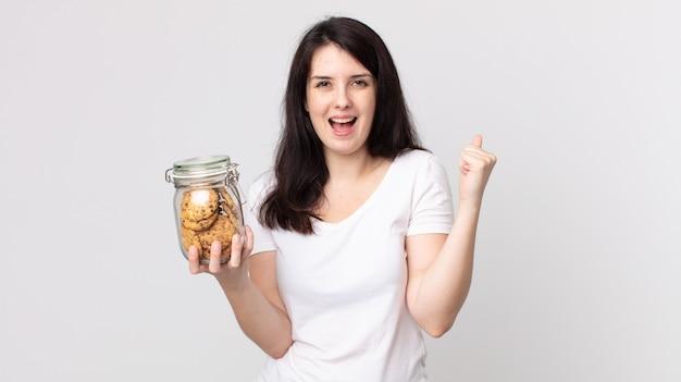 Bella donna che si sente scioccata, ride e celebra il successo e tiene in mano una bottiglia di vetro per biscotti
