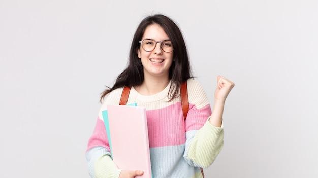 Bella donna che si sente scioccata, ride e celebra il successo. concetto di studente universitario