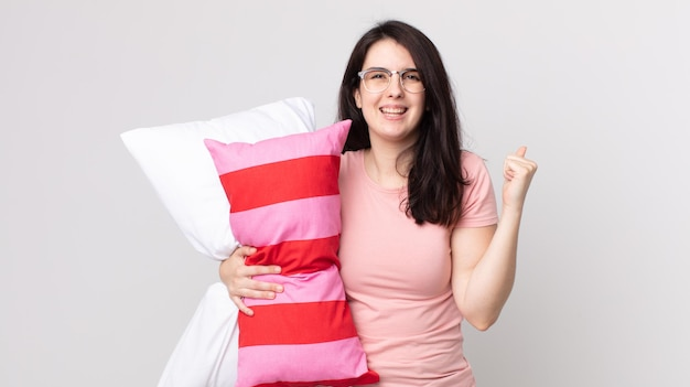 Bella donna che si sente scioccata, ride e celebra il successo indossando un pigiama e tenendo in mano un cuscino