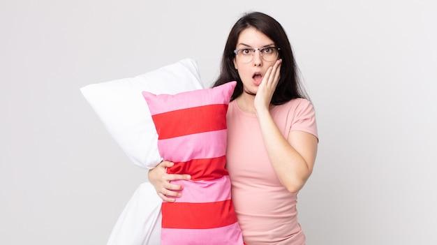Bella donna che si sente scioccata e spaventata indossando un pigiama e tenendo in mano un cuscino