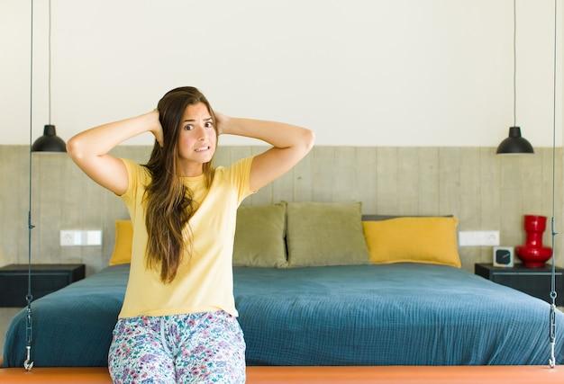 Bella donna che si sente stressata, preoccupata, ansiosa o spaventata, con le mani sulla testa, in preda al panico per errore