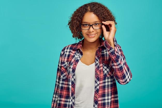 Bella donna con gli occhiali, muro blu, emozione positiva
