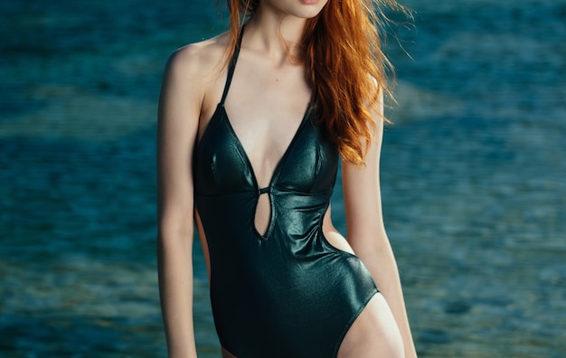 Pretty woman in costume da bagno verde occhiali da sole di lusso paesaggio. foto di alta qualità
