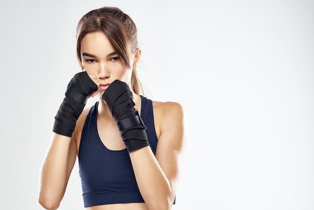 Le bende graziose della mano della donna perforano il fondo isolato combattente di allenamento