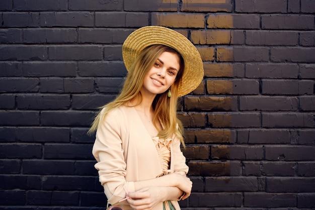 Bella donna in cappello che indossa occhiali da sole all'aperto nel muro di mattoni della città.
