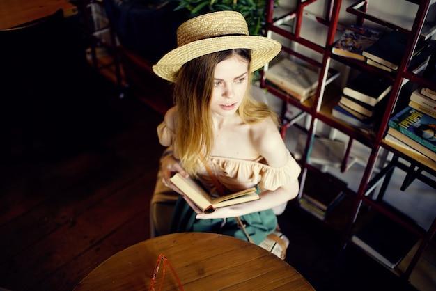 Bella donna in cappello con libro lettura vacanza interiore