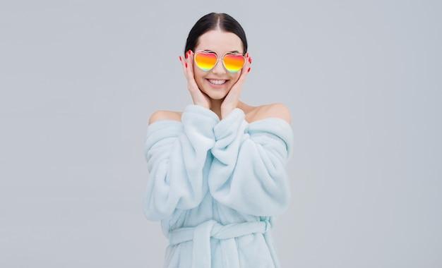 Bella donna in occhiali da sole arcobaleno a forma di cuore esprime emozioni gioiose