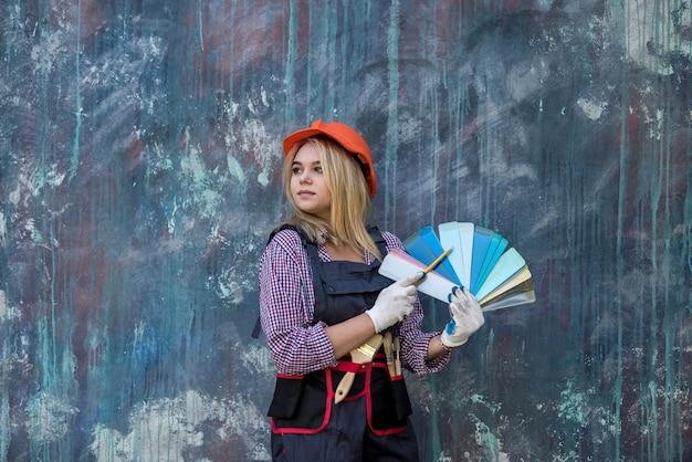 Bella donna in casco e uniforme pronta per la riparazione a casa, tenendo la tavolozza dei colori. design della casa