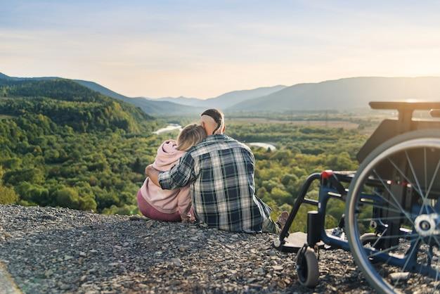 Bella donna e suo marito incapace di riposo insieme vicino alla sua sedia a rotelle sulla collina.
