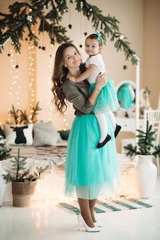 Bella donna che tiene la figlia nelle mani, in piedi in studio decorato con rami di abete e ghirlanda di luce